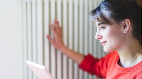 Smarthome-Angebote: Eine Frau prüft mit ihrer Hand die Heizung und schaut auf ein Tablet