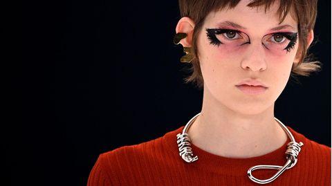 Das Model trägt eine silberne Kette in Galgenform von Givenchy