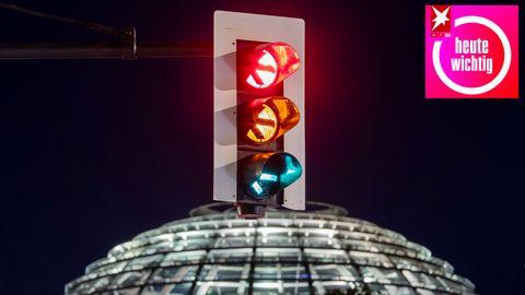 Eine Ampel vor der Kuppel des Reichstagsgebäudes leuchtet in einer Langzeitbelichtung in allen drei Phasen