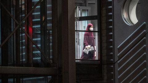Eine verschleierte Frau mit einer Maske verlässt den Gangway einer Chartermaschine.