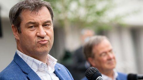 Markus Söder im Vordergrund mit einem leidenden Laschet im Hintergrund