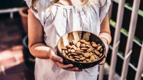 Ein Mädchen hält eine Schale mit Bittermandeln in den Händen