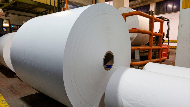 Papier liegt auf großen Rollen in einer Papierproduktionsfabrik
