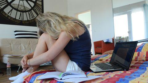 Eine junge Frau sitzt auf einem Bett und legt den Kopf auf ihre Knie, neben ihr ein Laptop.