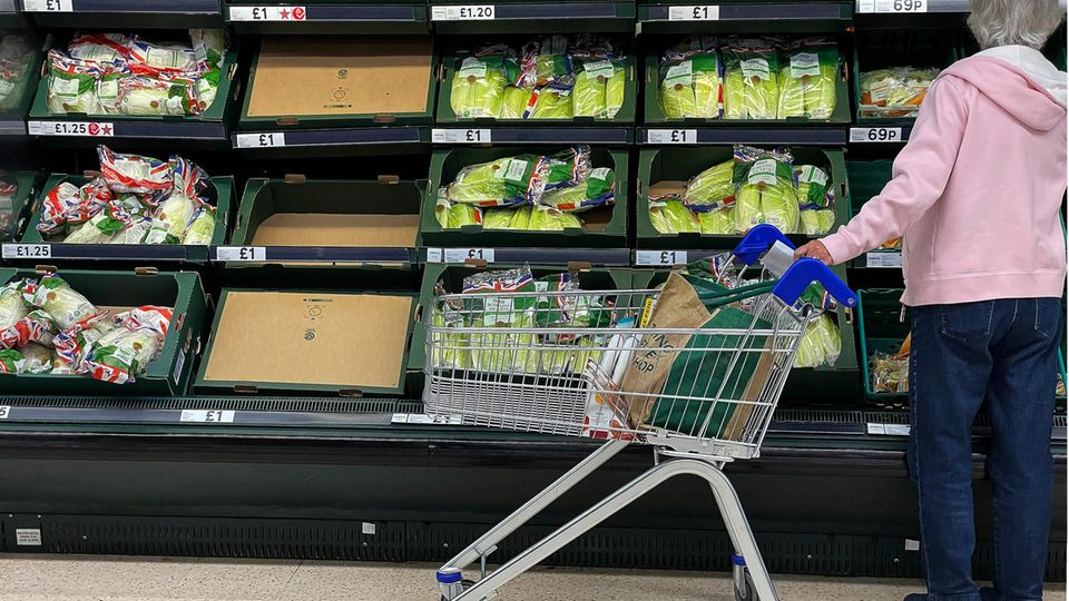 Eine Frau steht vor teilweise leeren Regalen in einem Supermarkt.