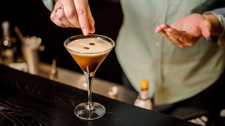 Espresso Martini: Ein Barkeeper garniert den vollendeten Espresso Martini mit drei Kaffeebohnen.