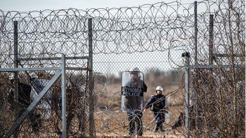 Ein griechischer Polizist steht an einem Loch im Zaun an der griechisch-türkischen Grenze