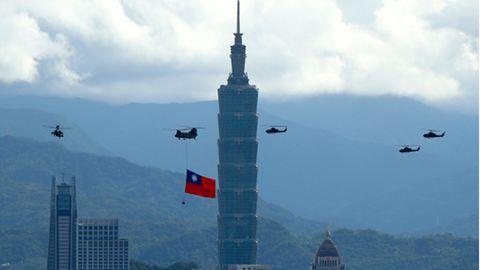 """Ein Militärhubschrauber zieht eine riesige Taiwan-Fahne hinter sich her und fliegt vor""""Taipei 101""""vorbei"""