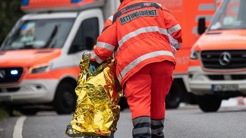 Ein Kind wird nach dem Unfall bei Frankfurt am Main von einer Notfallsanitäterin betreut