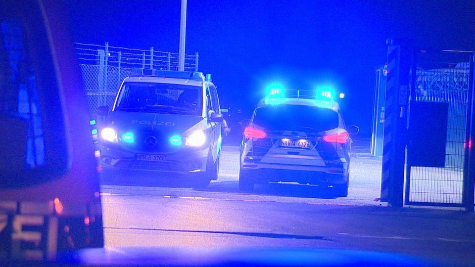 Polizisten passieren in Polizeifahrzeugen ein Tor am Flughafen Weeze