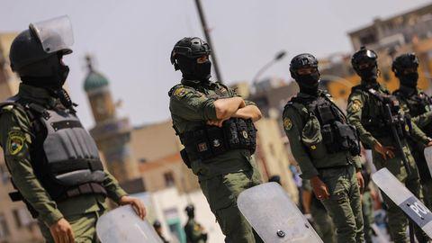 Sicherheitskräfte in Schutzkleidung stehen vor ihren abgestellten Schildern abseits einer Demonstration
