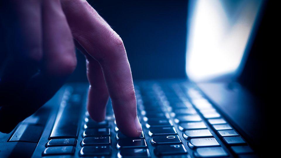 Finger tippt auf einer Tastatur, dunkle Umgebung und Gegegnlicht