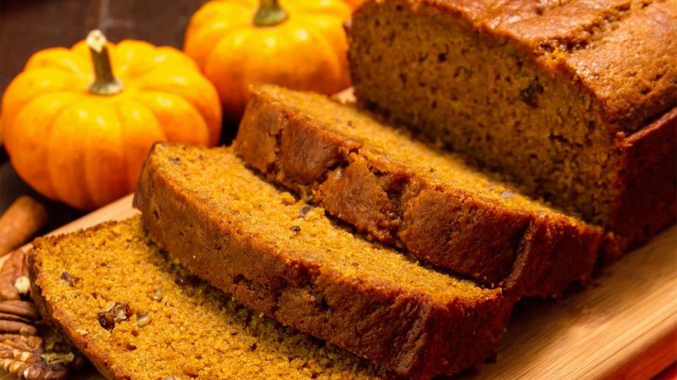 Das Bild zeigt ein dunkelbraunes Brot auf einem Holzbrett. Im Hintergrund sind Kürbisse zu sehen.