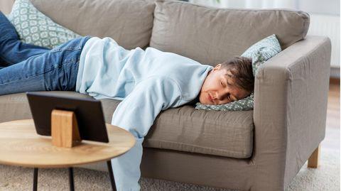 Ein Mann liegt auf einer Couch und schaut auf ein Tablet