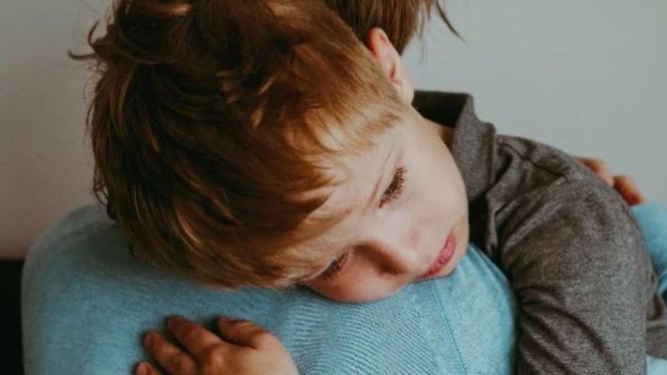 Ein Vater hält ein trauriges Kind auf dem Arm.