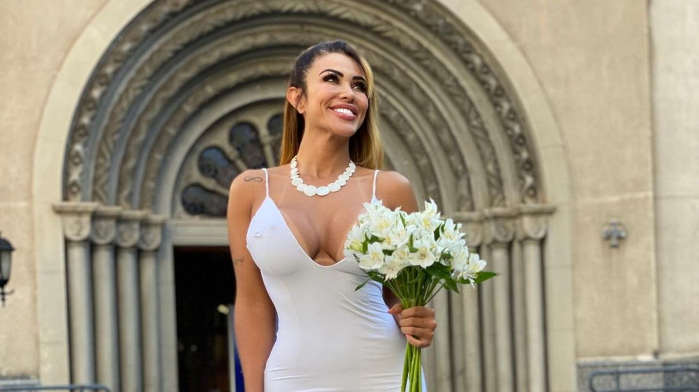 Die brasilianische Influencerin Chris Galêra trägt ein weißes Brautkleid und steht alleine vor einer Kirche