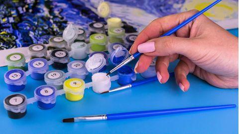 Eine Frau malt ein Bild nach Zahlen