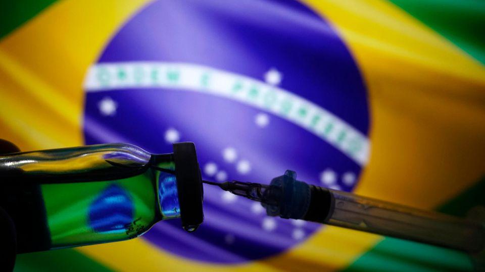Die Flagge Brasiliens zusammen mit einer Spritze und Impfstoff