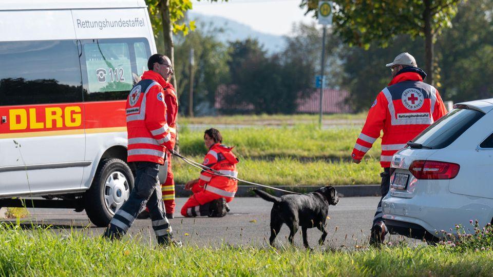 Bayern, Furth im Wald: Einsatzkräfte mit einem Suchhund stehen auf einem Parkplatz an der deutsch-tschechischen Grenze
