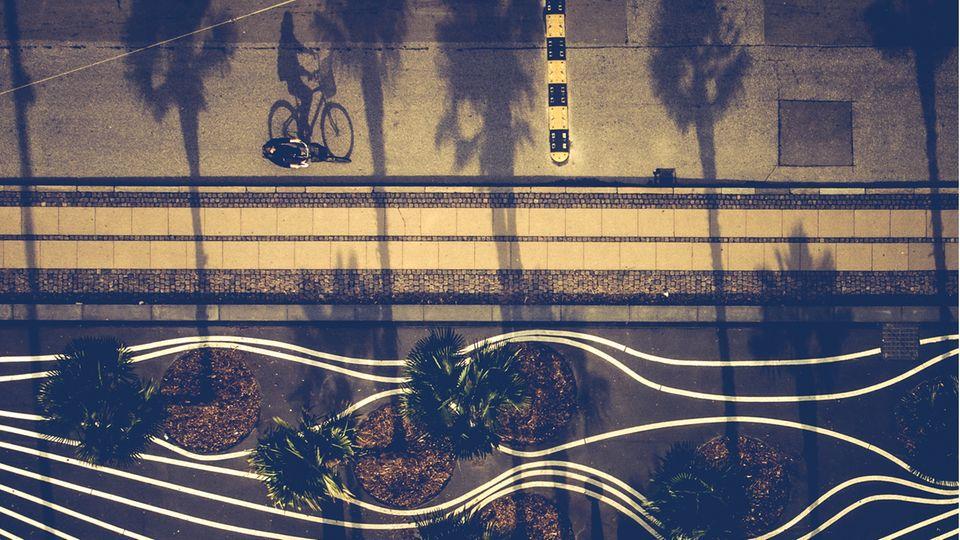 Drohnenfoto eines Fahrradfahrers der durch den Superkilen Park, ein mit weißen Linien gestalteter Platz, fährt.