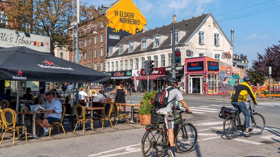 Fahrradfahrer halten an Ampel, im Hintergrund bunte Cafés.