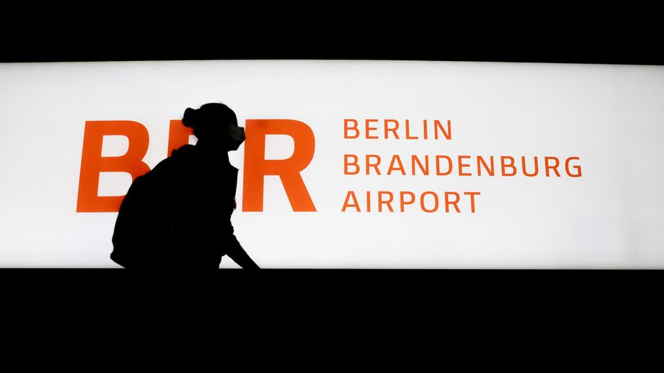 Passagierin läuft an einem beleucteten Schild BER Berlin Brandenburg Airport vorbei