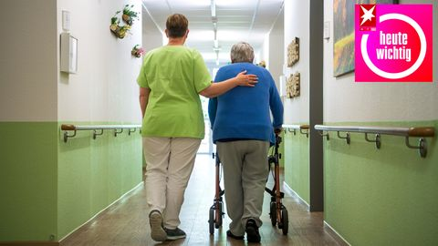 Altenpflegerin begleitet ältere Frau über den Gang