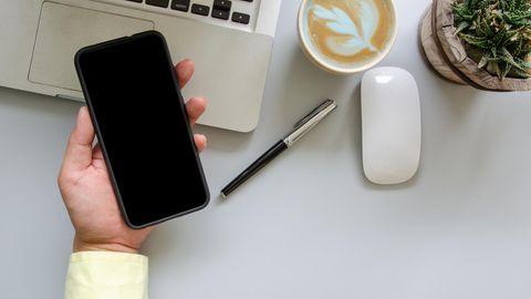 Das iPhone X liegt in einer männlichen Hand.