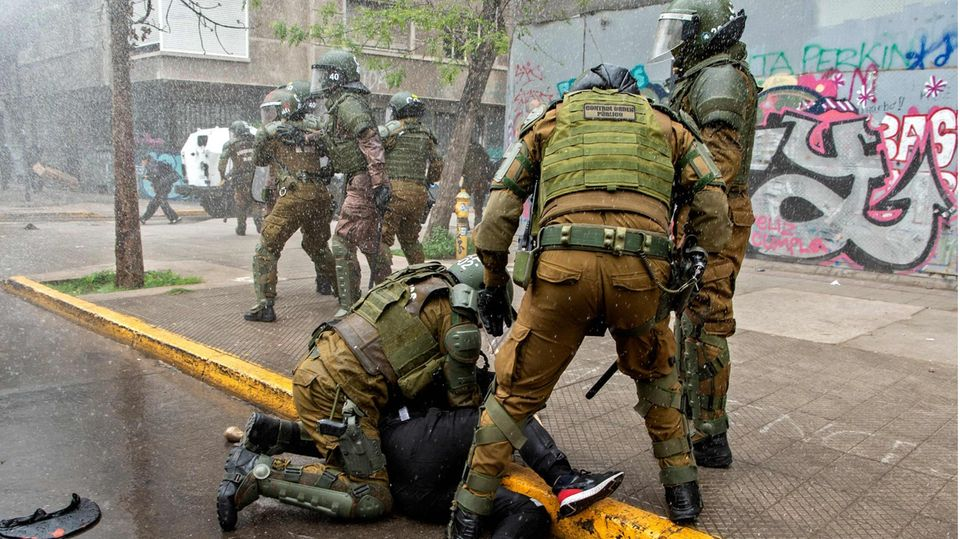 Sicherheitskräfte halten einen Demonstranten bei den Protesten in Chile fest