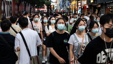 Passanten in der chinesischen Stadt Wuhan in der Provinz Hubei tragen Mund-Nasen-Schutz
