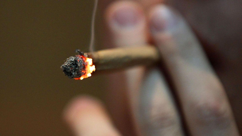 Ein Mann raucht einen Joint.