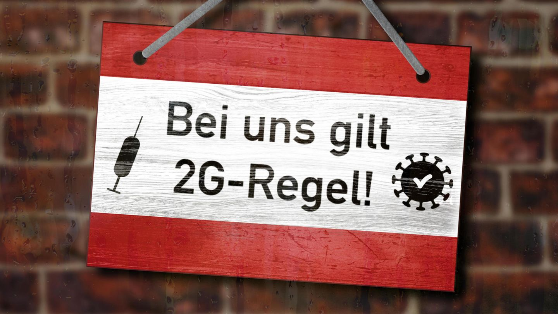 "Schild mit Aufschrift ""Bei uns gilt 2G-Regel!"" hängt an einer Wand"
