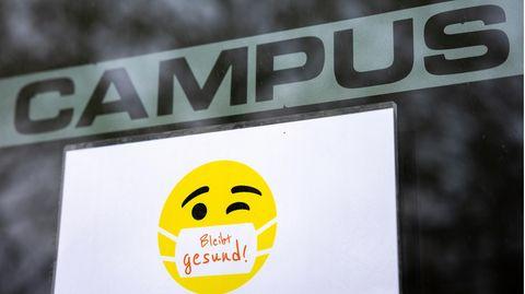 """Ein Schild an der Sporthalle der Technischen Universität Ilmenau weist mit dem Spruch """"Bleibt gesund!""""auf die Maskenpflicht hin"""