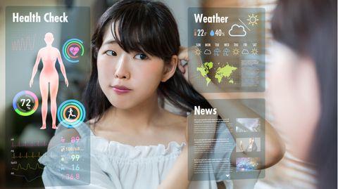 Smarte Spiegel: Eine Frau frisiert sich vor einem smarten Spiegel die Haare.