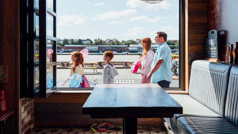 Familie mit zwei Kindern steht vor einem Restaurant