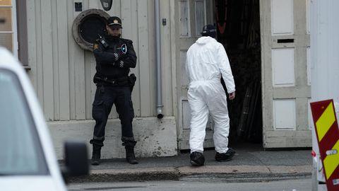 Techniker der Polizei geht nach einer Gewalttat mit fünf Toten und zwei Verletzten in ein Gebäude, vor dem ein Polizist Wache steht