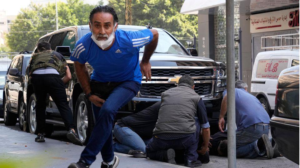 Libanon, Beirut: Personen gehen hinter einem Auto in Deckung