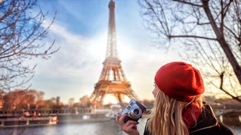 Junge Frau sitzt mit einer Kamera in der Hand vor dem Eiffelturm in Paris
