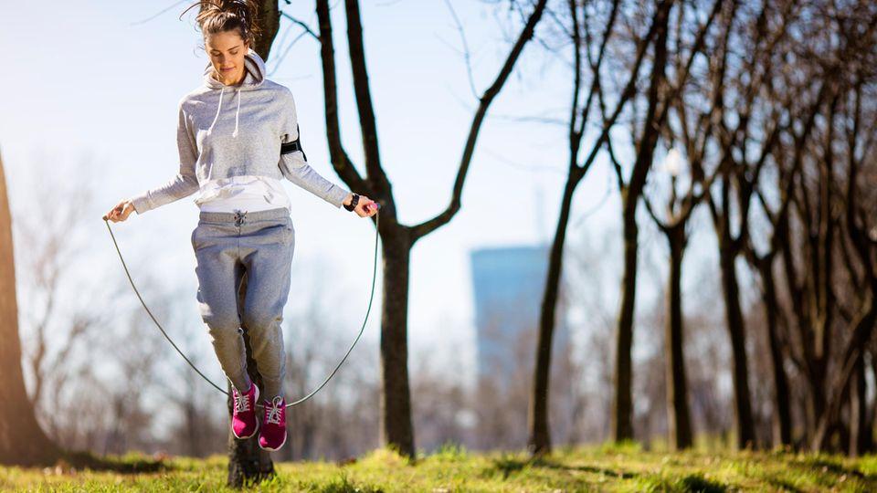 Seilspringen: Frau trainiert in einem Park mit einem Springseil