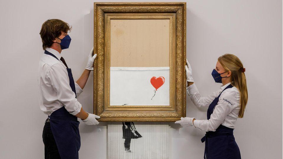 Mitarbeiter von Sotheby's zeigen das geschredderte Werk Girl with Balloon von Banksy