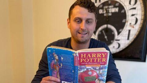 Mann namens Harry Potter hält einen Harry Potter-Roman in der Hand