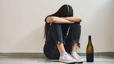 Mädchen neben Weinflasche