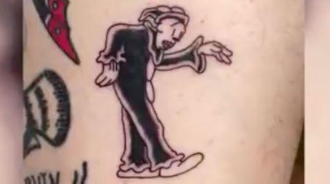 Ein frisches Tattoo auf Haut zeigt tanzenden Clown