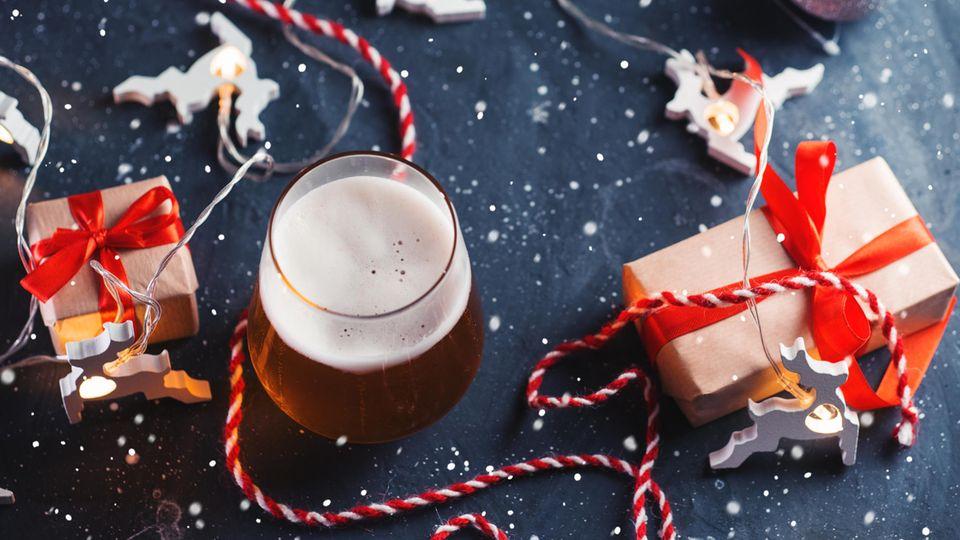 Bier-Adventskalender: Ein frisch gezapftes Bier steht zwischen Geschenken.