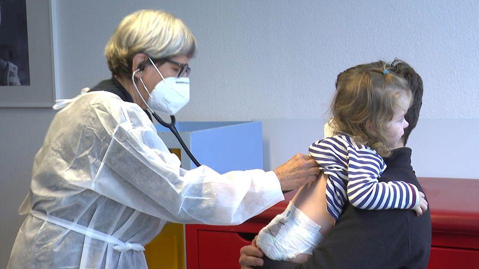 Eine Ärztin horcht ein Kind auf dem Arm ihres Vaters ab.