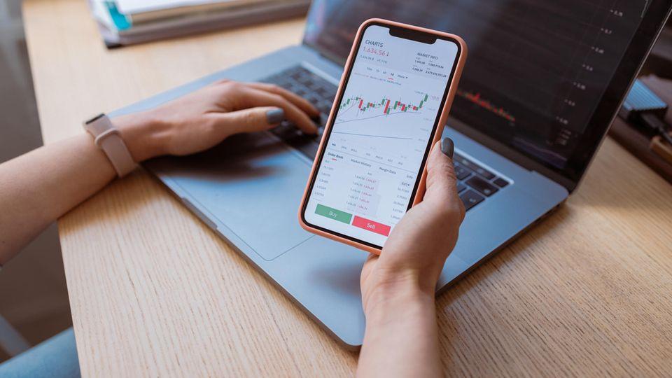 Podcast Stunde Null Trade Republic: Eine Frau ruft auf ihrem Smartphone Informationen zu einem Aktienkurs ab