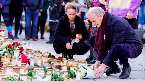 Norwegens Ministerpräsident Jonas Gahr Støre hockt an der improvierten Gedenkstätte für die Opfer von Kongsberg