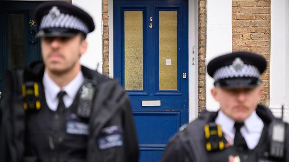 Polizisten stehenvor einem Haus im Londoner Stadtteil Kentish Town Wache