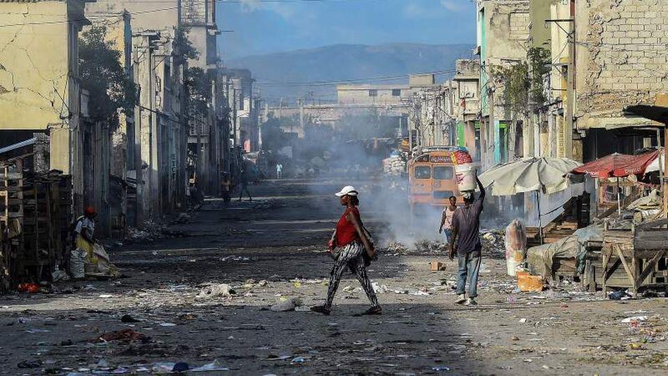 Mehrere Menschen laufen über eine Straße in der Downtown von Haitis Hauptstadt Port-au-Prince