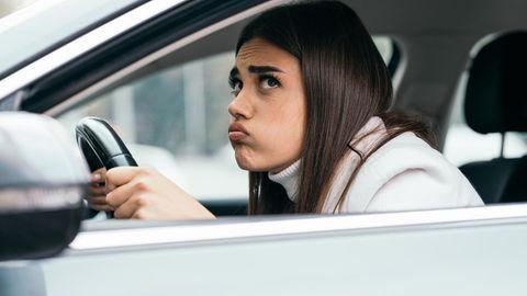 Eine Frau sitzt mit angespanntem Gesichtsausdruck in einem Auto